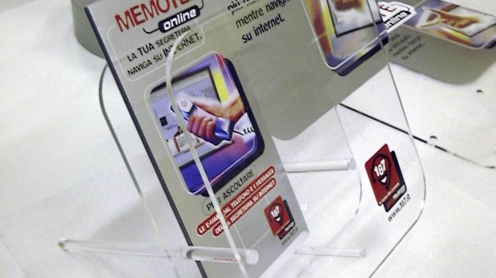 """Espositori e Materiali P.O.P. - Espositore da banco """"Telecom"""" realizzato in plexiglas trasparente, grafica adesiva."""