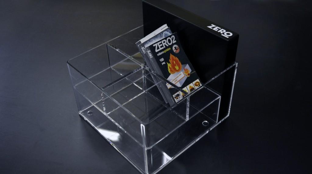 """Espositori e Materiali P.O.P. - Espositore da banco """"Zero"""" in plexiglas trasparente e MDF laccato nero, grafica adesiva."""